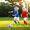 103987606-kids-play-football-on-outdoor-field-children-score-a-goal-at-soccer-game-girl-and-boy-kicking-ball-r.jpg
